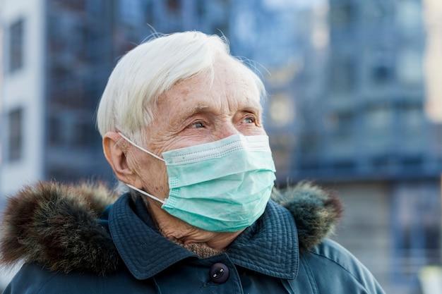 Starsza kobieta jest ubranym medyczną maskę w mieście