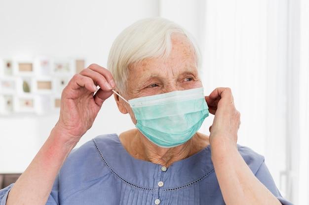 Starsza kobieta jest ubranym medyczną maskę