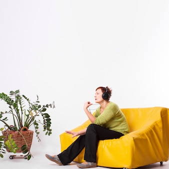 Starsza kobieta jest usytuowanym na kanapie i słucha muzykę