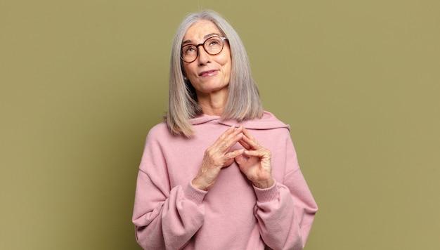 Starsza kobieta knuje intrygi i konspiruje, myśli podstępne sztuczki i oszustwa, przebiegłość i zdradę