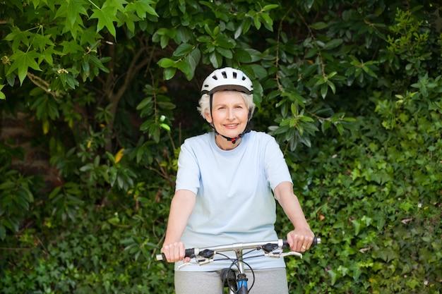 Starsza kobieta kolarstwo górskie na zewnątrz