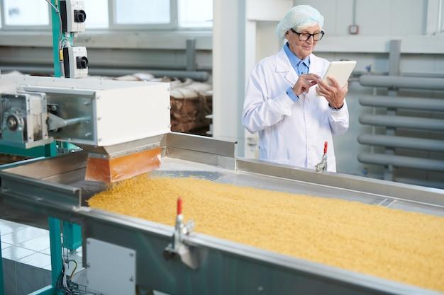 Starsza kobieta kontroluje produkcję żywności