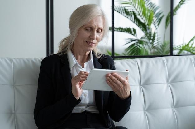 Starsza kobieta korzysta z cyfrowego tabletu siedząc na kanapie w domu korzystanie z technologii przez osoby starsze
