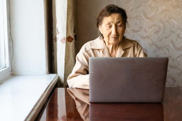 Starsza kobieta korzysta z laptopa. wygląda na bardzo zaskoczoną. surfowanie w przeglądarce i mediach społecznościowych. laptop na stole. korzystanie z technologii w koncepcji starości