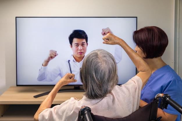 Starsza kobieta korzystająca z usługi online fizjoterapii w domu.