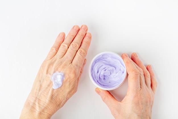 Starsza kobieta kremowanie jej ręce z bliska. kosmetyczna pielęgnacja nawilżająca dla starej skóry. pielęgnacja i leczenie dłoni przeciw starzeniu się. maść do leczenia stawów dla osób starszych.