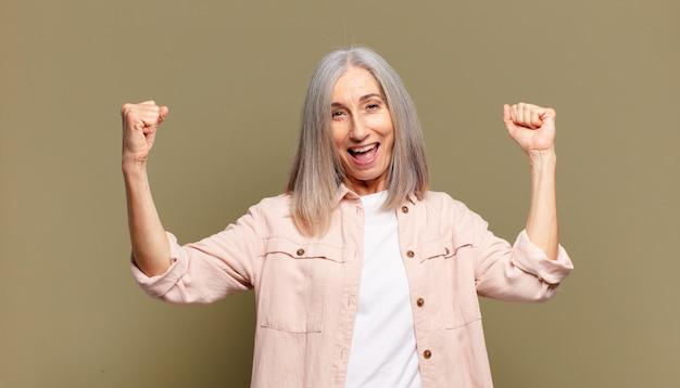 Starsza kobieta krzycząca triumfalnie, wyglądająca jak podekscytowana, szczęśliwa i zaskoczona zwycięzca, świętuje
