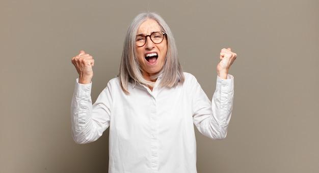 Starsza kobieta krzyczy agresywnie z gniewnym wyrazem twarzy lub z zaciśniętymi pięściami świętuje sukces