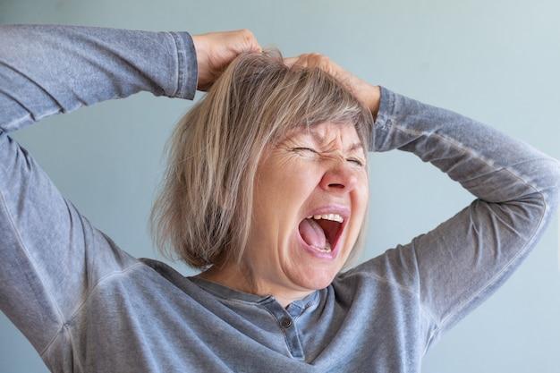 Starsza kobieta krzyczy na depresję uzależnioną od stresu i alkoholizmu. zdrowie psychiczne. koncepcje dokumentu społecznego. koncepcje dokumentu społecznego.