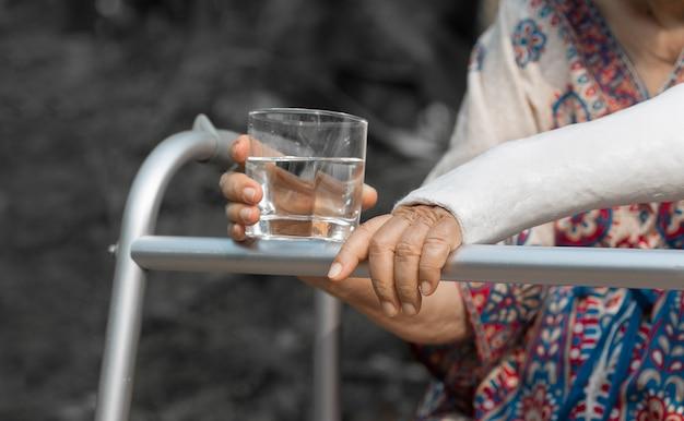 Starsza kobieta łamał nadgarstek używać piechura w podwórku.