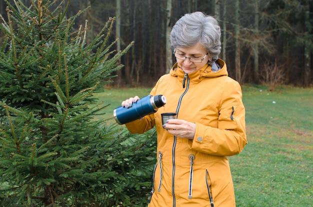 Starsza kobieta leje gorący napój z termosu na zewnątrz w lesie. starszy kobieta w żółtym płaszczu na spacerze w zimnie