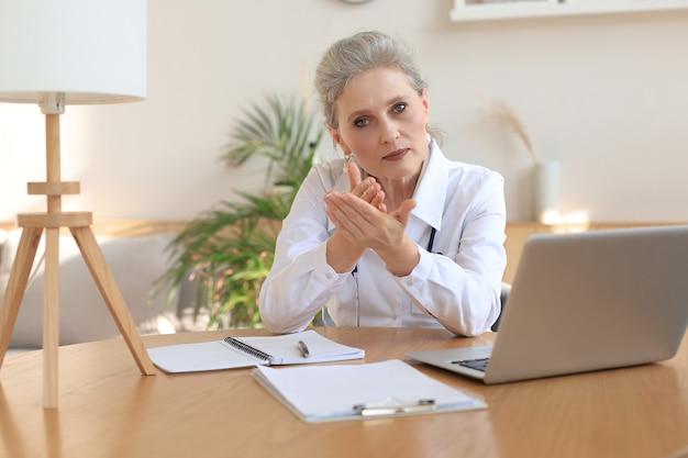 Starsza kobieta lekarz terapeuta nosząca zestaw słuchawkowy rozmowa wideo rozmawiająca z kamerą internetową konsultująca wirtualnego pacjenta online przez czat wideokonferencyjny.