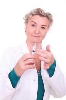 Starsza kobieta lekarz ze strzykawki