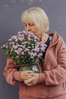 Starsza kobieta lubi zapach kwiatów. wiekowa samica niosąca doniczkę ze świeżymi kwiatami
