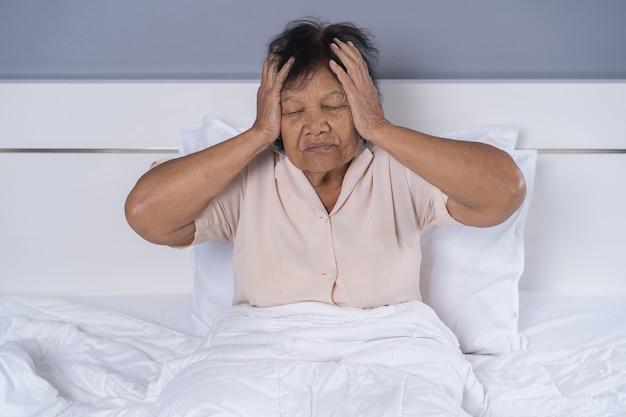 Starsza kobieta ma ból głowy na łóżku