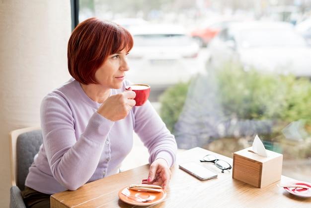 Starsza kobieta ma kawę