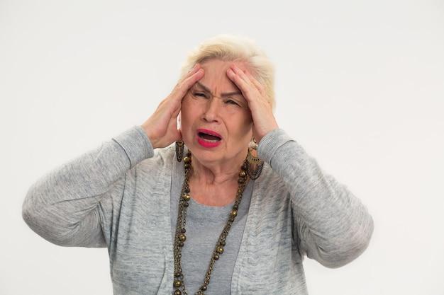 Starsza kobieta ma panią z bólem głowy trzymającą głowę na białym tle