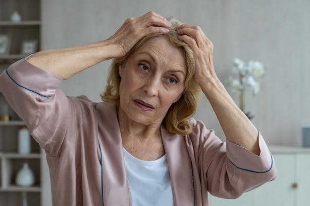 Starsza kobieta ma problemy z wypadaniem włosów, starsza kobieta patrzy na swoje włosy w lustrze i jest