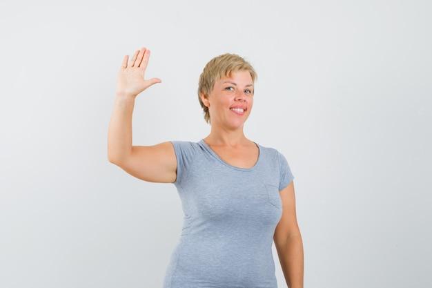 Starsza kobieta macha ręką, by pożegnać się w szarym t-shircie i wygląda na zadowoloną