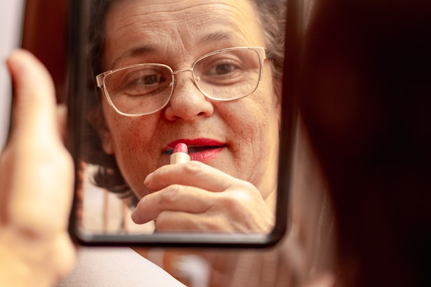 Starsza kobieta maluje usta szminką, dbając o swoją urodę. poważna starsza kobieta nakłada szminkę przed lustrem. odbicie kobiety w lustrze