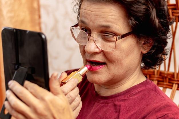 Starsza kobieta maluje usta szminką, dbając o swoją urodę. poważna starsza kobieta nakłada szminkę przed lustrem