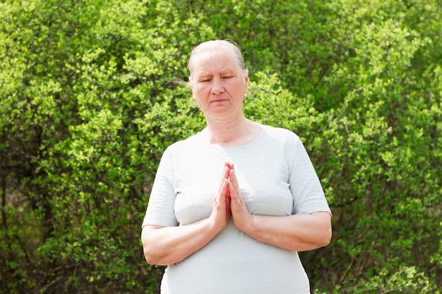 Starsza kobieta medytuje z założonymi rękami.