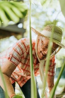 Starsza kobieta miewa skłonność rośliny w jej ogródzie
