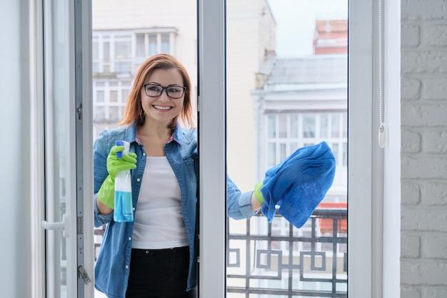 Starsza kobieta mycie okien w domu na wiosnę, kobieta z butelką detergentu z rozpylaczem szmatą