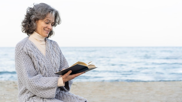 Starsza kobieta na plaży czyta książkę