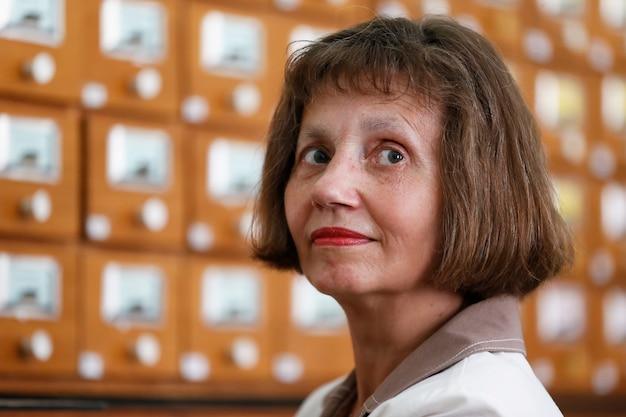 Starsza kobieta na tle cel bibliotecznych. bibliotekarz retro.