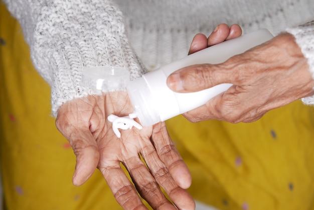 Starsza kobieta nakłada krem kosmetyczny na skórę