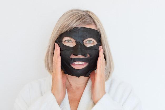 Starsza kobieta nakłada na twarz czarną maseczkę kosmetyczną. koncepcja anty wieku. dojrzała kobieta twarz po zabiegu uzdrowiskowym. zabiegi kosmetyczne spa. klinika chirurgii plastycznej, kosmetologia, nowy senior