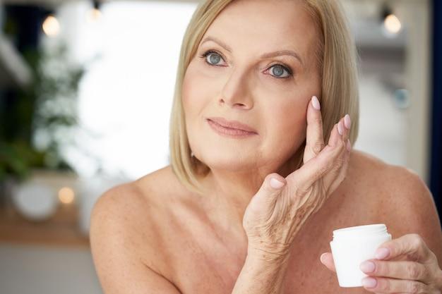 Starsza kobieta nakładająca krem do twarzy w łazience
