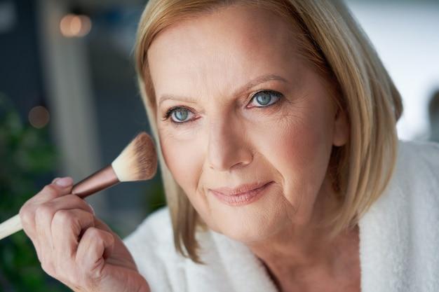 Starsza kobieta nakładająca makijaż w łazience