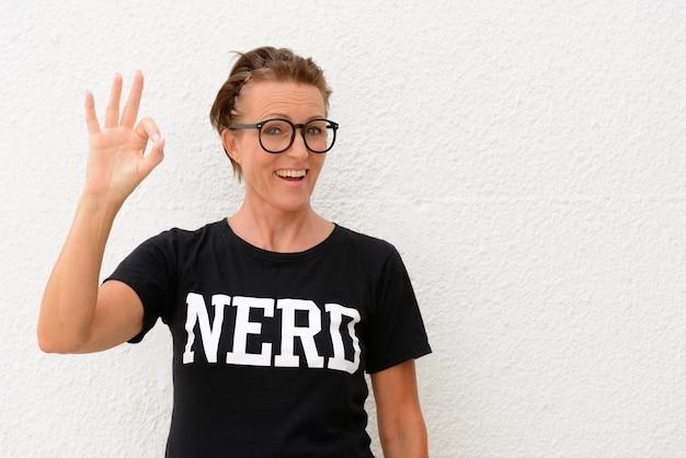 Starsza kobieta nerd noszenie dużych okularów i stojącej samodzielnie podczas uśmiechu