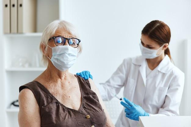 Starsza kobieta nosząca maskę medyczną w szpitalu na szczepienie paszport ciążowy