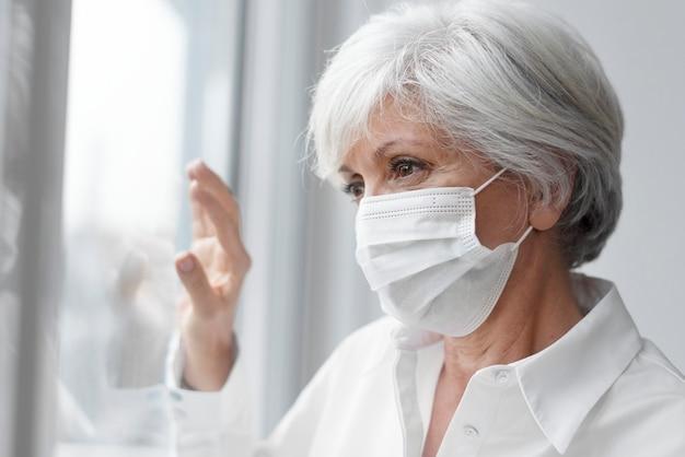 Starsza kobieta nosząca maskę na twarz podczas pobytu w domu