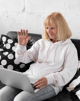 Starsza kobieta o rozmowie wideo z laptopem