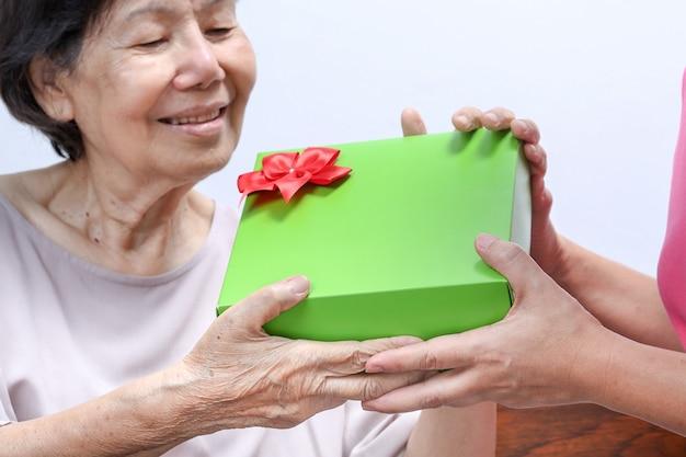 Starsza kobieta odbiera prezent od córki