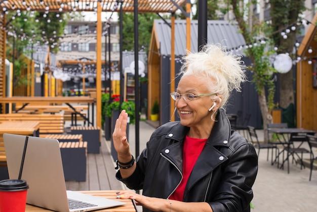 Starsza kobieta odpoczywa w kawiarni na świeżym powietrzu komunikuje się za pomocą wideo true wireless