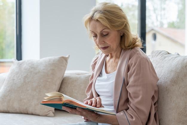 Starsza kobieta odpoczywa w salonie, czyta powieść