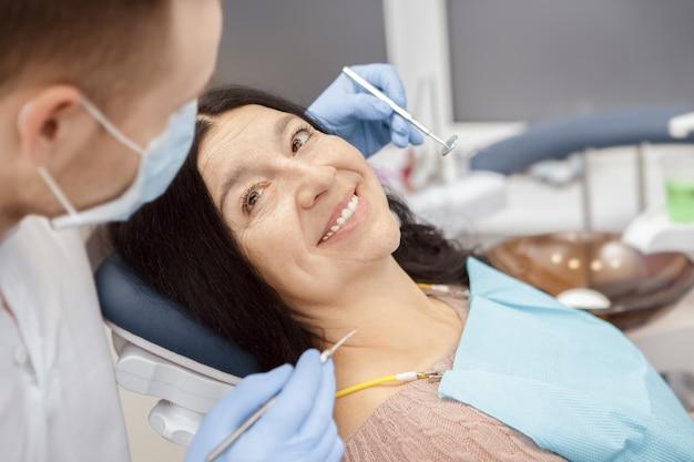 Starsza kobieta odwiedza dentysty przy stomatologiczną kliniką