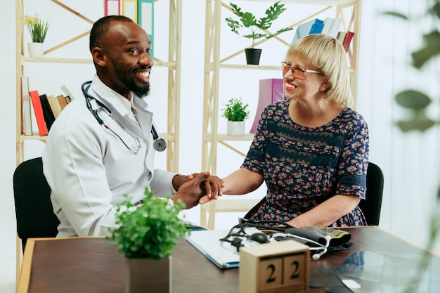 Starsza kobieta odwiedzająca terapeutę w klinice w celu konsultacji i sprawdzenia stanu zdrowia.