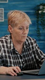 Starsza kobieta oglądając szkolenia biznesowe