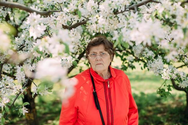 Starsza kobieta okulary jasne czerwone kurtki okulary