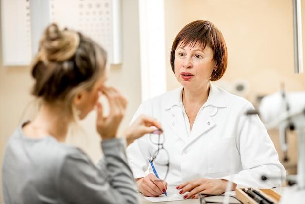 Starsza kobieta okulista z młodą pacjentką podczas konsultacji w gabinecie okulistycznym