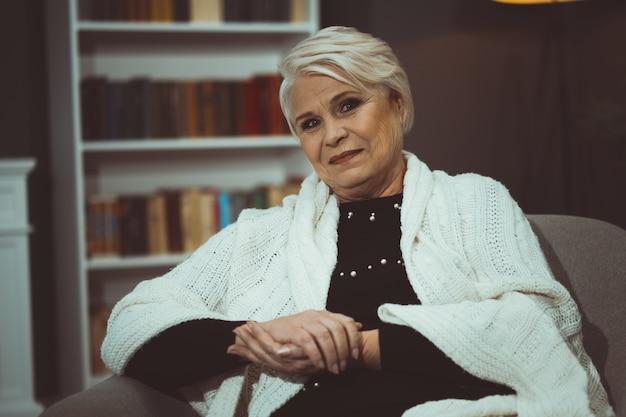 Starsza kobieta ono uśmiecha się siedząc w krześle