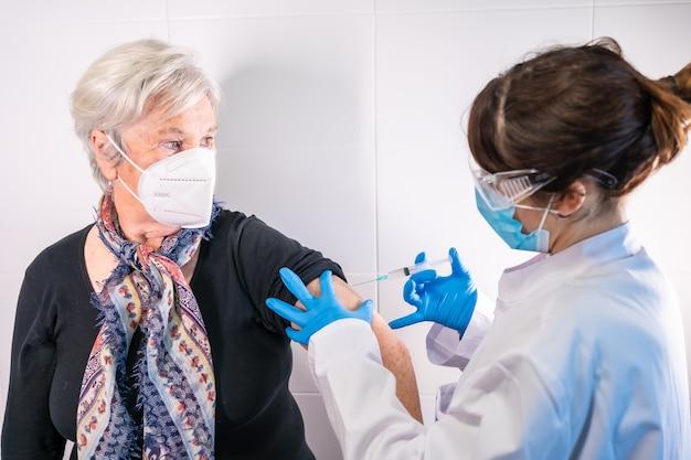 Starsza kobieta otrzymująca od lekarza zastrzyk szczepionki przeciwko koronawirusowi. przeciwciała uodporniają populację.