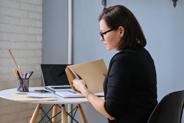 Starsza kobieta otwierając kopertę z papierowymi dokumentami. kobieta siedzi przy biurku z laptopem, notatnikiem biznesowym