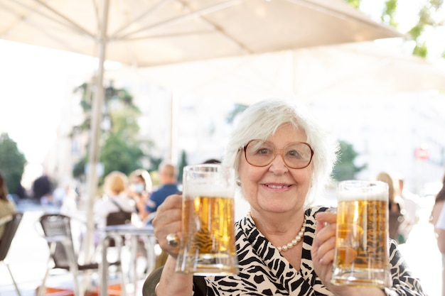 Starsza kobieta, patrząc na kamery, siedząc na tarasie, pijąc piwo. kobieta z dwoma piwami w dłoni